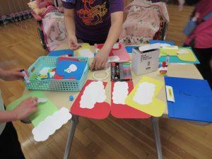 テーブルの上に赤や青や黄色の紙が広がっており、クリスマスの飾りの形に切り取ったものが並んでいる様子