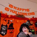 オレンジのハロウィンの飾りをバックに仮装する利用者さんの様子