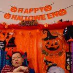 オレンジのハロウィンの飾りをバックにして仮装する利用者さんの様子
