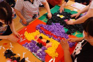 紫色の魔女と黒猫の形に丸めた紙を貼り付けている様子