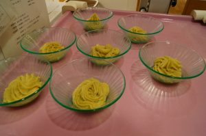 7枚の緑色のガラス製のお皿にクリーム色のスイートポテトが入って、テーブルに乗っている様子