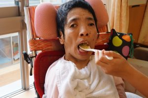 車椅子に持った利用者さんにスタッフがスプーンでスイートポテトを食べさせてあげている様子