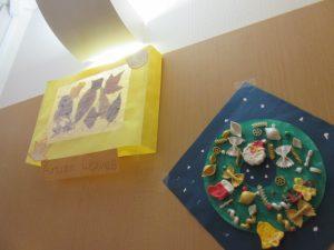 黄色の紙で貼り絵をした作品と紺色の土台の紙にサンタクロースやクリスマスの飾りをつけた作品の様子