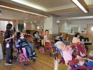 広いお部屋に車椅子に乗った利用者さん数人とスタッフ数人が集まっている様子