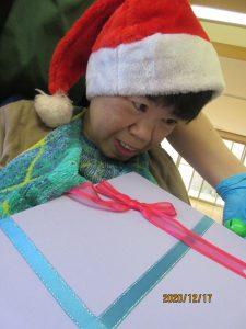 サンタの帽子をかぶった利用者さんがプレゼントの箱を持っている様子