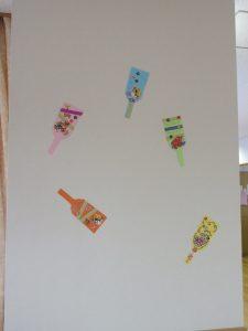 白い壁に紙で作った羽子板が貼ってある様子