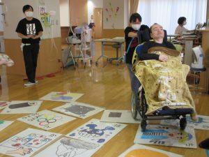 部屋にカルタがたくさん並んでいる横で車椅子に乗った利用者さんがいる様子