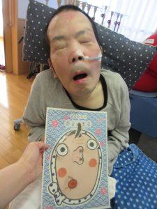 別の男性の利用者さんが福笑いの紙と一緒に写っている様子