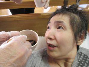 女性の利用者さんにカップに入ったおしるこを食べてもらっている様子