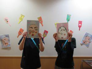 スタッフ2人が顔に福笑いの紙をあてて立っている様子