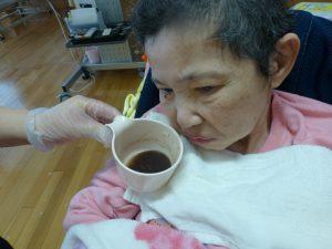 車椅子に乗った女性の利用者さんのそばにおしるこの入ったカップを近づけている様子