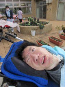 手前に車椅子で横たわる利用者さんと奥には2人のスタッフと一人の利用者さんが花壇のそばに写っている様子