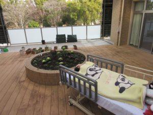 中庭の花壇のそばにベッドの利用者さんが横たわっている様子