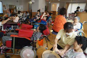 デイルームで大勢の車椅子に座った利用者さんが集まっている様子