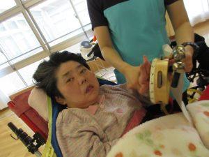 車椅子に乗った別の利用者さんのお顔の近くにタンバリンと鈴を持たせてあげている様子