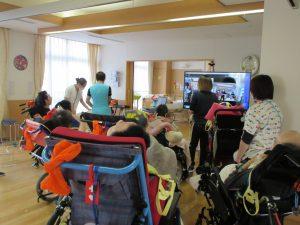 広いお部屋に車椅子の利用者さんやスタッフが大きなテレビの前に集まっている様子