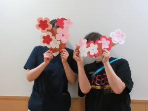 紙で作った梅と一緒に写るスタッフ2人の様子