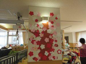 紙で作ったピンクの梅と一緒に写る利用者さんの様子