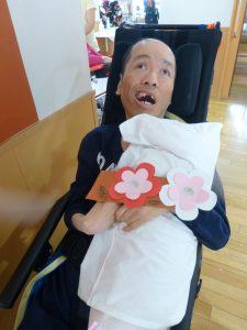 ピンクの紙で作った梅と一緒に写る利用者さんの様子