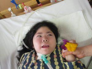別の利用者さんがベッドに横たわりながらm押し花用の花と一緒に写る様子