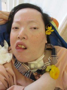 別の女性の利用者さんが耳にオレンジの花を飾っている様子