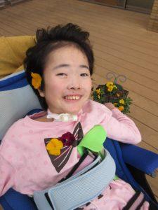 別の女の子の利用者さんが耳にオレンジの花を飾り、胸元にはオレンジの花と紫の花を飾ってもらって嬉しそうな表情でいる様子