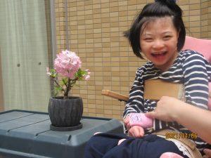 盆栽の桜と一緒に笑顔で写る女の子の利用者さん