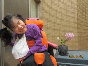 1人の女の子の利用者さんが盆栽のピンクの桜を一緒に笑顔で写っている様子
