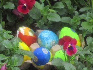 綺麗な色に色付けされたタマゴが花壇に並んでいる様子