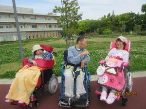 3人の車椅子に乗った利用者さんが広い緑の芝生をバックに並んでいる様子