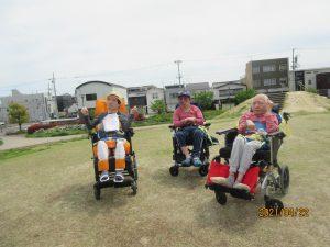 別の3人の利用者さんが芝生をバックに車椅子に乗って並んでいる様子