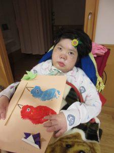 車椅子に座った女性の利用者さんが画用紙のこいのぼりと一緒に写っている様子