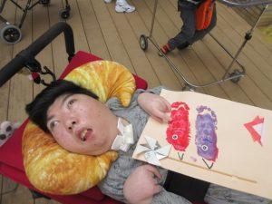 車椅子の利用者さんと画用紙上の赤と紫のこいのぼりが一緒に写っている様子
