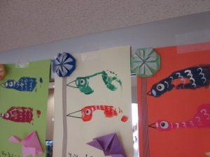 壁に青色や赤色と緑色などの9匹のこいのぼりが飾ってある様子