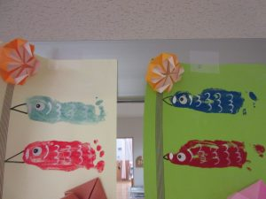 部屋の壁に水色や赤色や青色などの4匹のこいのぼりが貼り付けて飾ってある様子