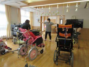 デイルームで車椅子に乗った利用者さんやスタッフが数人集まっている様子