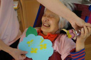 色紙で作ったアジサイの花を持って、鈴も手に持ち笑顔の女性の利用者さんの様子