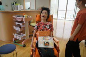 車椅子に乗った女性の利用者さんが笑顔で記念撮影をしている様子