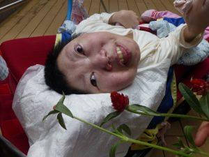 車椅子に横たわっている女性の利用者さんと赤い千日紅の花と一緒に写っている様子