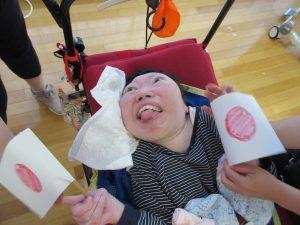 車椅子に乗った女性の利用者さんが両端に手作りの日の丸の旗を持って笑顔でみえる様子