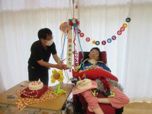 手作りの飾りの中で誕生日のお祝いをしてもらっている車椅子に座った利用者さんの様子