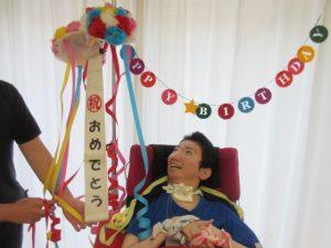 おめでとうと書いた飾りを見ながら笑顔の車椅子の利用者さんの様子