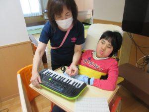 鍵盤ハーモニカを前にスタッフと一緒に弾いている利用者さん
