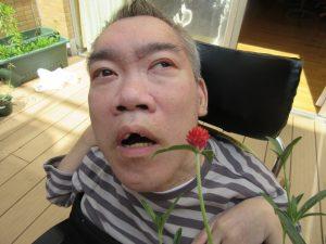 1輪の赤い千日紅の花と男性の利用者さんが一緒に写っている様子