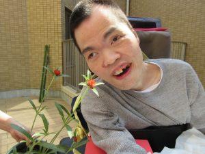 笑顔の男性利用者さんと赤い千日紅の花が一緒に写っている様子