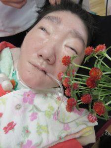 赤い千日紅の花束と女性の利用者さんが一緒に写っている様子
