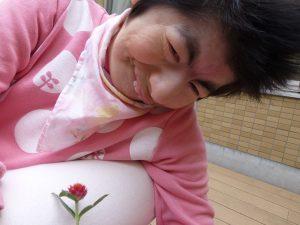 女性の利用者さんが微笑んでいる隣に一輪の赤い千日紅の花が写っている様子