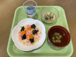 緑色のトレイにちらし寿司とサラダ、水色のキレイなぜりーなどがのっている様子