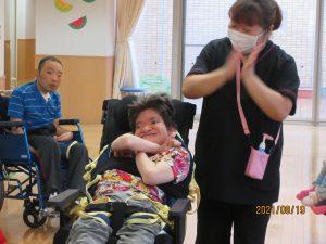 車椅子に乗った女性の利用者さんと手をたたいているスタッフが並んでいる様子