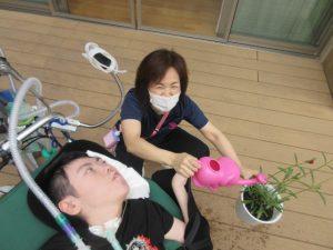 植木鉢の千日紅に、車椅子に座った利用者さんと一緒にスタッフがじょうろで水やりをしている様子